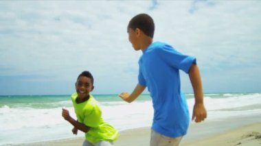 Young African American brothers playing together on beach — Stock Video