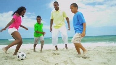 Football game of ethnic father wit young sons and teenage daughter on beach — Stock Video