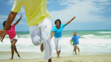 Smiling diverse parents playing together sons and daughter on beach — Stock Video