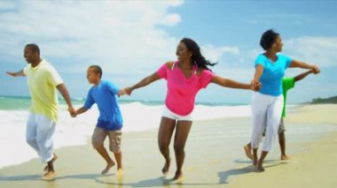Ethnic parents running together young children on beach shot on RED EPIC — Stock Video