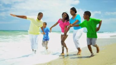 African American family laughing and running together in surfs — Stock Video