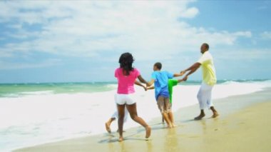 Ethnic family walking on holiday together on beach holding hands — Stock Video