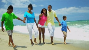 African American family enjoying summer vacation walking together on beach — Stock Video
