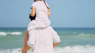 Caucasian girl being carried on fathers shoulders on beach — Stock Video