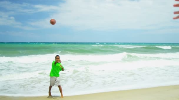 Young ethnic friends catching American football's ball on beach — Vidéo