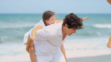 Laughing girl being carried on fathers shoulders on beach mother watching — Stock Video