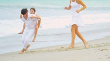 Caucasian happy parents having fun together daughter piggyback on beach — Stock Video