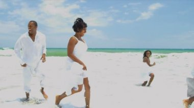 Ethnic family enjoying time together walking and laughing on beach — Stock Video