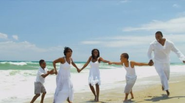 African American family together playing and laughing by ocean — Vídeo stock