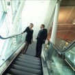 Business couple meeting on moving escalator - Stock Photo