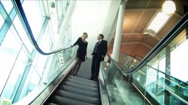Business couple meeting on moving escalator