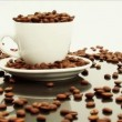 Coffee beans overflowing from white coffee cup - Stock Photo