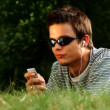 Stock Video: Young male lying in the park listening to music
