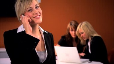 Beautiful blonde businesswoman chats on the cell with her colleagues — Stock Video