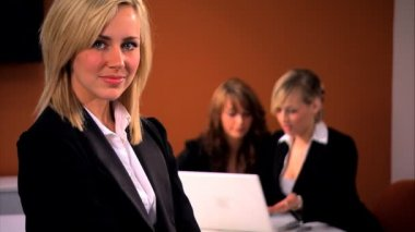 Blonde businesswoman with team in background — Stock Video