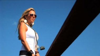 Elegant blonde woman standing on jetty and looking over the sea — Stock Video
