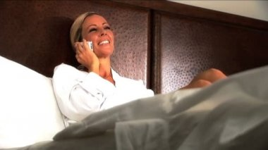 Attractive blonde woman on her hotel bed talking on her cell phone — Stock Video