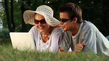 夏の日の公園でラップトップを使用して若いカップル — ストックビデオ