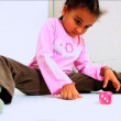 Cute little african american girl rolling a dice — Stock Video