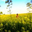 Stock Video: Little african american girl playing in a field of yellow rapeseed