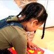 Cute little african american girl opening birthday gifts - Foto Stock