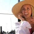 Attractive blonde girl talking on the phone on board her yacht - Foto Stock