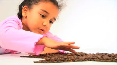 Cute little girl forming star shape from coffee beans — Stock Video