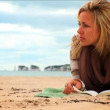 Beautiful young blonde girl reading on the beach - Foto Stock