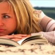 Beautiful young blonde girl reading on the beach - Photo