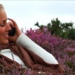 Cute blond girl talking on mobile phone in purple heather — Stock Video