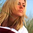 Attractive blong girl writing diary on the beach — Stock Video