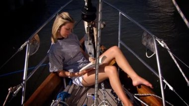 Beautiful young blonde girl relaxing with a book aboard a luxury yacht — Stock Video