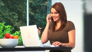 A beautiful brunette businesswoman works from home with a laptop & Cell phone