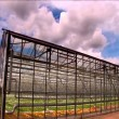 Timelapse clouds roll over a large greenhouse farm - Stock Photo