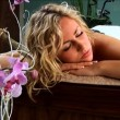 Beautiful blonde girl having hot stones massage treatment - Stock Photo