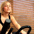 Beautiful blonde girl enjoys working out at the gym — Stock Video #19405569