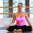 Attractive slim brunette girl practising yoga exercises at a gym - Стоковая фотография