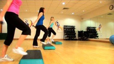 Schöne junge Mädchen, die aerobe-Übungen in einem Fitnessstudio zu tun — Stockvideo