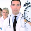 Medical team - doctor holding alarm clock — Stock Video #19410949