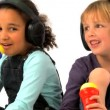 Little african american girl & blonde boy wearing earphones & singing into toy microphone — Stock Video