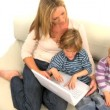 Stock Video: Mother and her cute sons sitting on the sofa and using laptop