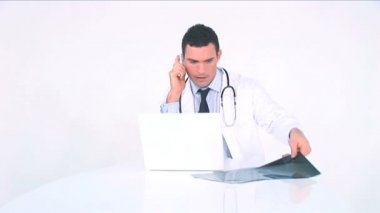 Doctor examining x-ray and consulting it on the phone — Stock Video #19410067