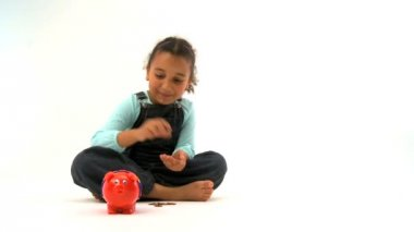 Cute little african american girl inserting coins into a piggy bank — Stock Video