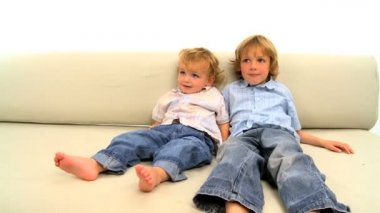Two little blonde boys lying on the sofa on white background