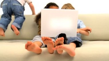 Cute young african american & caucasian cousins playing & using laptop on white sofa