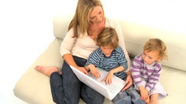 Mother and her cute sons sitting on the sofa and using laptop — Stock Video