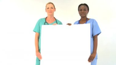 Female medical team holding blank notice-board isolated on white
