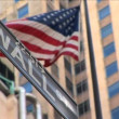 Wall Street & American flag flying - Stock Photo