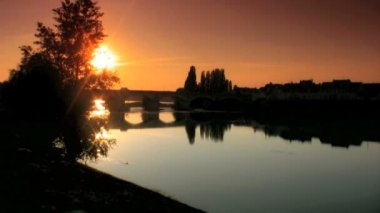 Bridge & shoreline reflected in the river at sunset in Loire valley — Stock Video