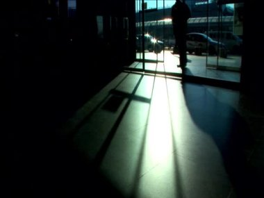 Commuters passing through the airport terminal in silhouette — Stock Video